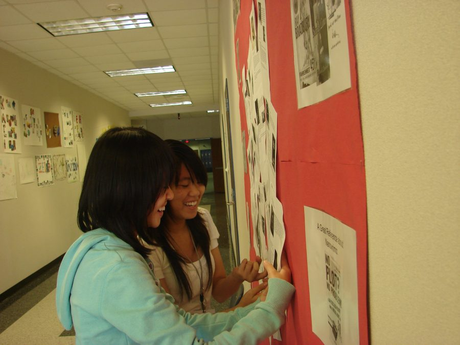 During the Thursday Writing Club Meeting, Sophomores Janique A. and Abby L. look over author profiles on the Nanowrimo display.