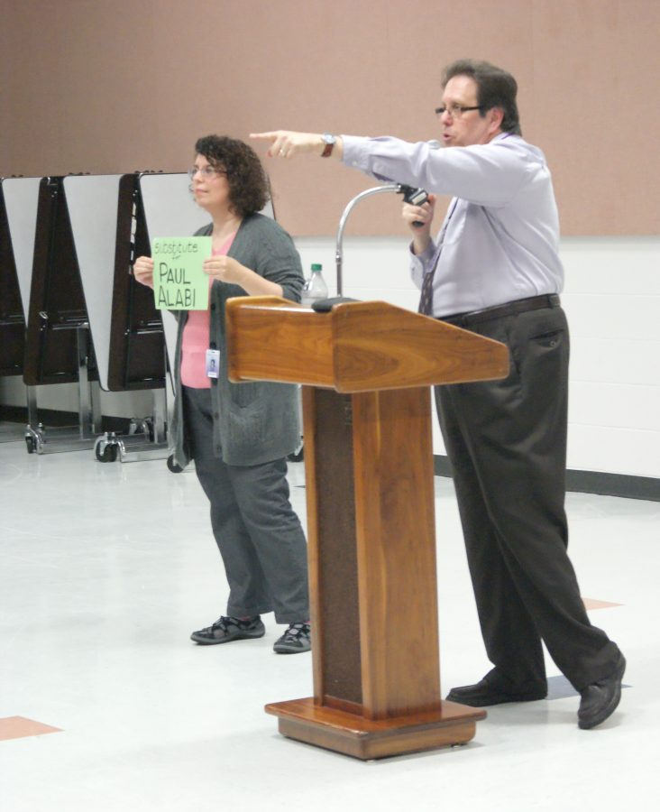 Senior class sponsor Eileen Caetta stands in senior Paul A.'s place as auctioneer Steve Levine auctions him off.