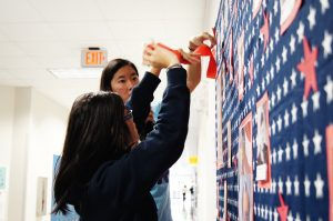 Seniors Tam Vu and Linda Le use streamers to decorate the traditional Veterans' Day wall.