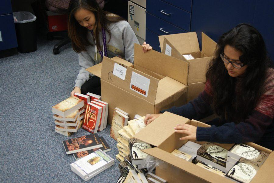 Sabrina Dang and Alondra Tristan sort the newly arrived books received from the grant