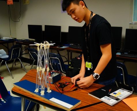 Freshman Linh Nguyen tests out his elevator mechanism by varying weight, speed, and time in a project this fall.