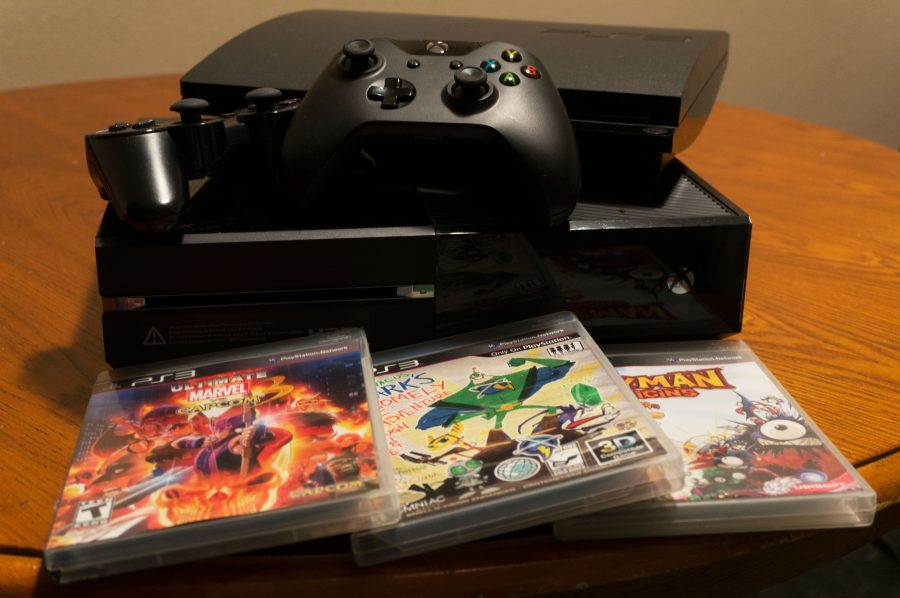 From+top%3A+Playstation+3+and+a+controller%2C+Xbox+One+and+a+controller%2C+%E2%80%9CUltimate+Marvel+Vs.+Capcom+3%2C%E2%80%9D+%E2%80%9CRachet+and+Clank+All+4+One%E2%80%9D+and+%E2%80%9CRayman+Orgins%E2%80%9D