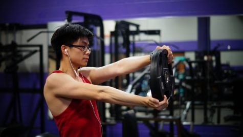 Senior James Dang twists his arms while holding a weight to strengthen his forearms.