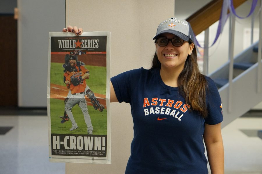 Foreign Language Teacher Michelle Zapata is one of many feeling the Astros' fever, decked out in Astros' gear while holding up an issue of the Houston Chronicle documenting the Astros' historical win.