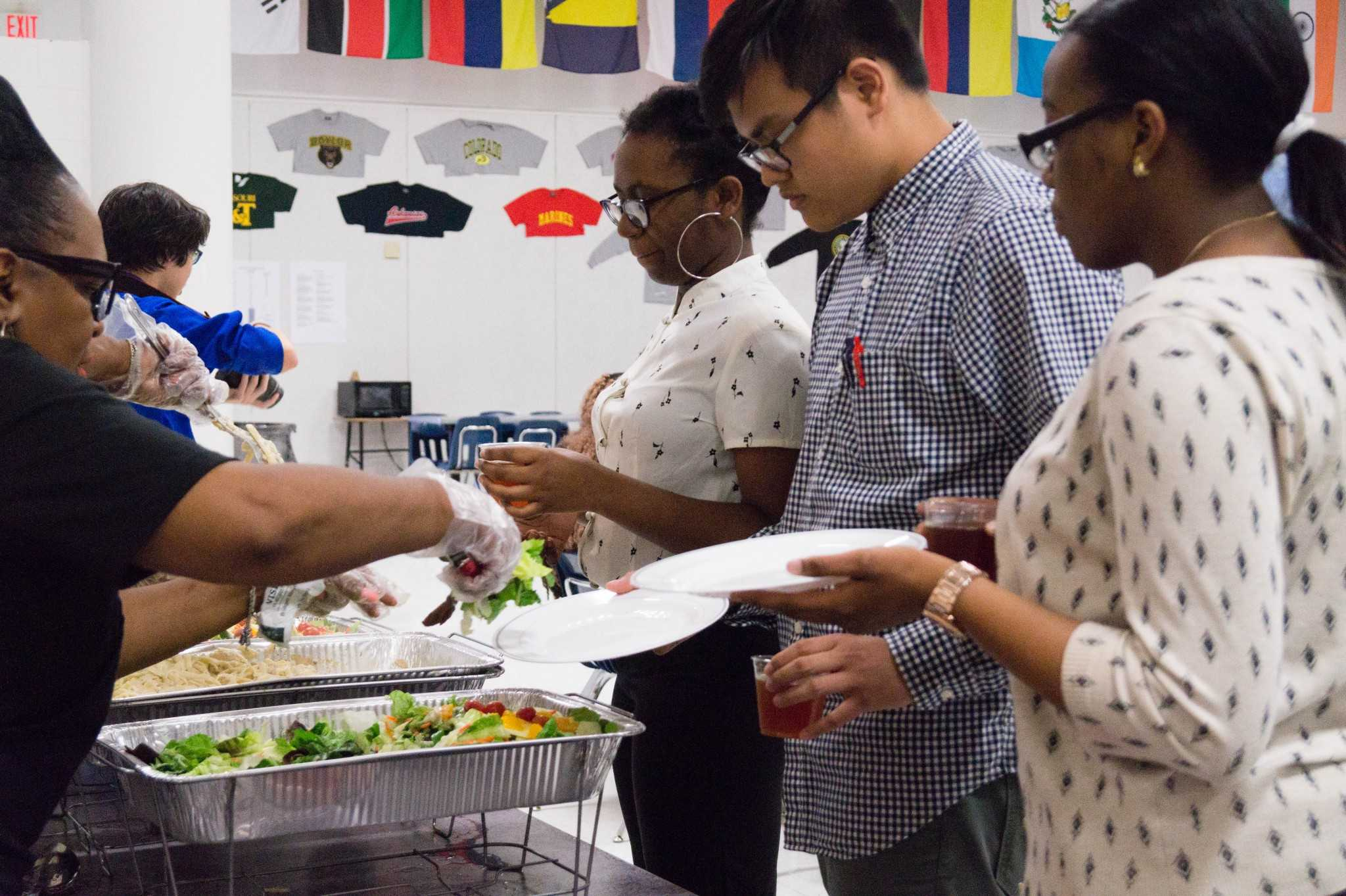 Duy Vo (12), Ashley Gwananji (12), and Vina Nweke (12) wait and anticipate on getting their delicious Alfredo and salad for the Eating Etiquette Workshop where they learn how they should eat in professional dinner settings.