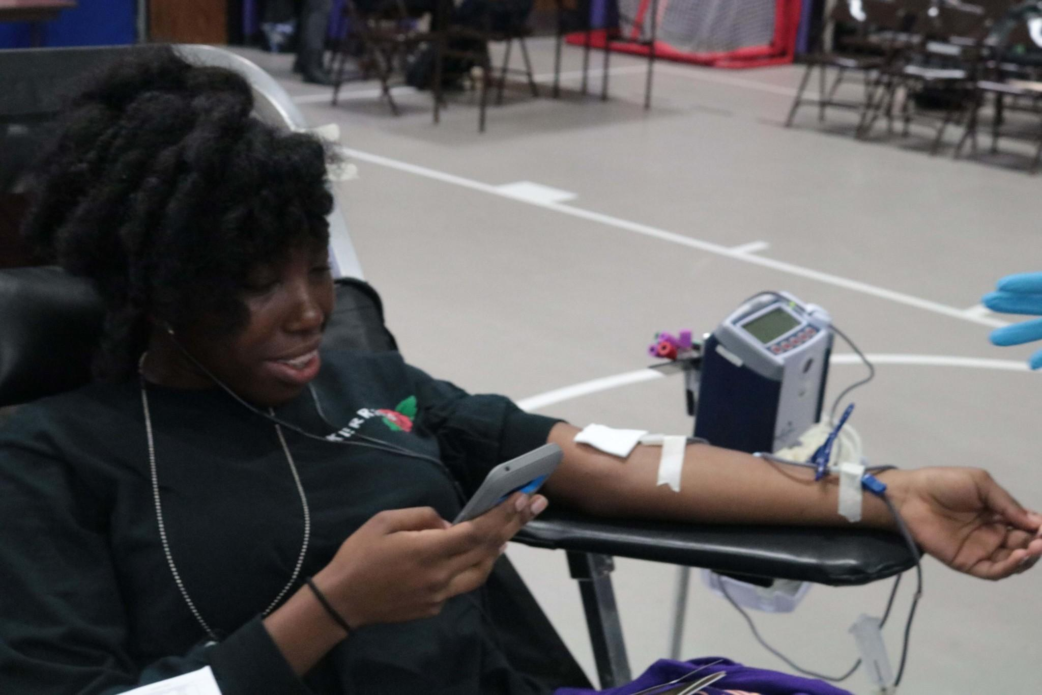 Dominique Carter, a junior, is getting her blood drawn while on her phone.
