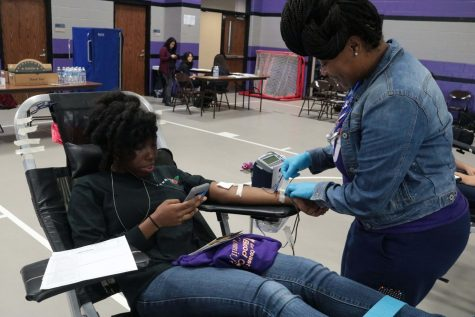 Henrietta Cole, the Gulf Coast Regional Blood Center phlebotomist, is drawing blood from Dominique Carter on September 2.
