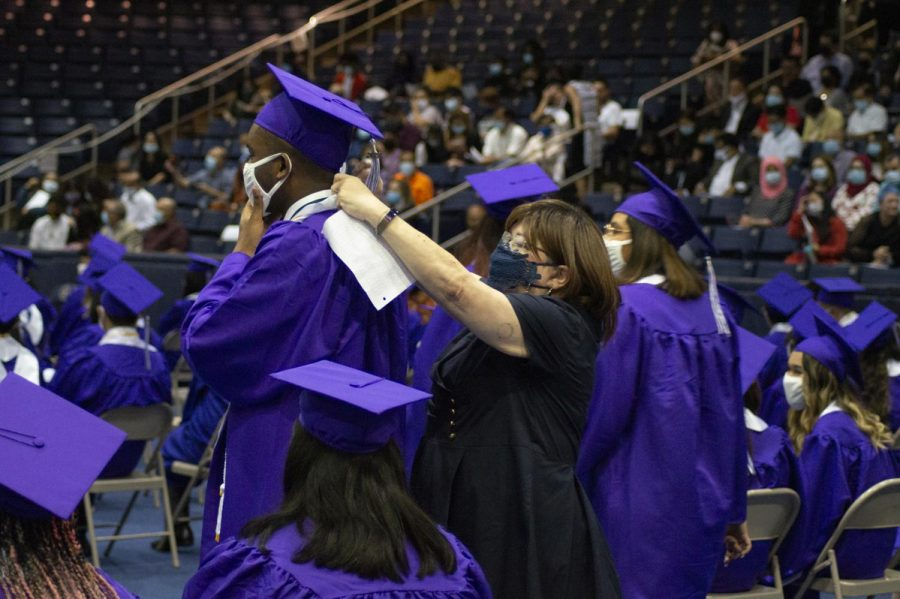 Gromyko Ngueyap gets assistance with his stole from technology specialist Cindi Payne.