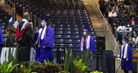 Principal Vinson Lewis fist-bumps Deborah Yang as Destiny Youngblood and Tiffany Zhang approach the stage
